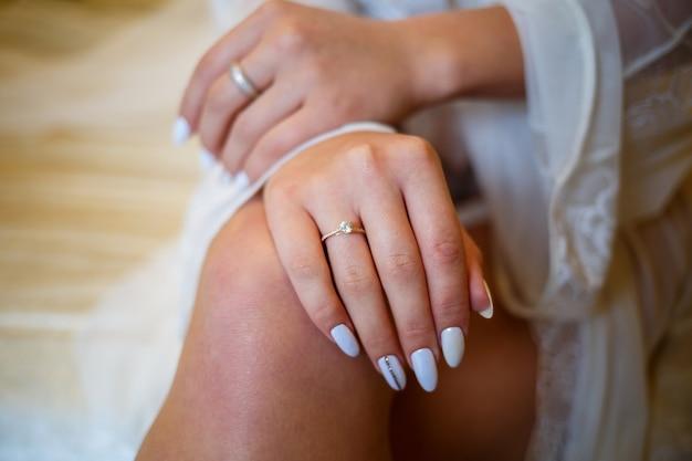 The bride's golden wedding ring on her finger on her wedding day
