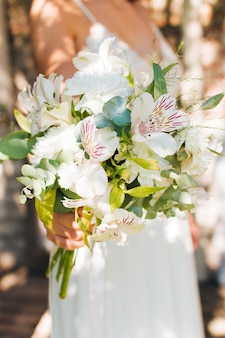 Bride's hand holding peruvian lily and gerbera flowers bouquet in hand