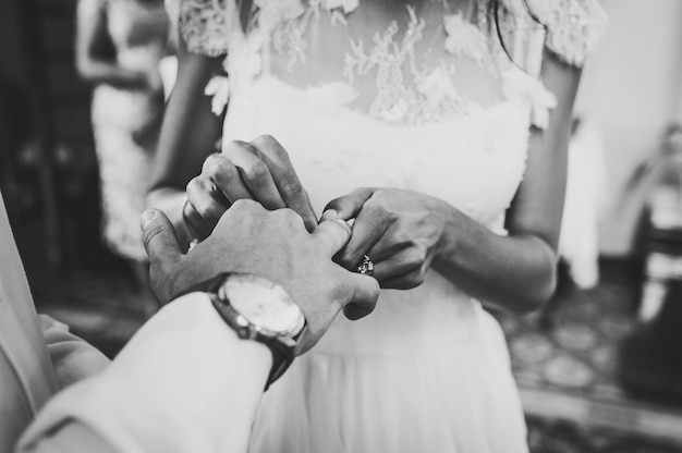 The bride's hand wears an engagement gold ring on the groom's finger. wedding day. hands with wedding rings. close up. black and white photo.
