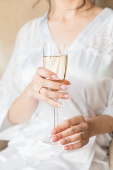 Bride's hand with beautiful manicure and engagement ring and champagne glass