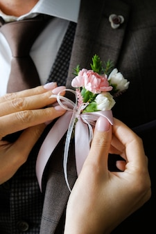 The bride's hands adjust the boutonniere on the groom's wedding jacket