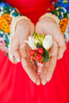 Bride's hands are keeping her groom's boutonniere