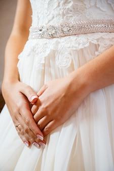 白いウェディングドレスに折りたたまれた花嫁の手