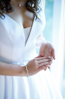 Bride's hands folded on a white wedding dress