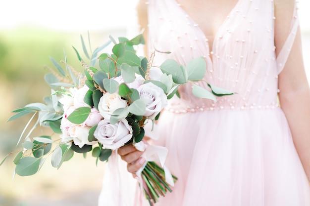 花嫁の手はバラの美しいブライダルブーケを持っています。ファインアート写真。