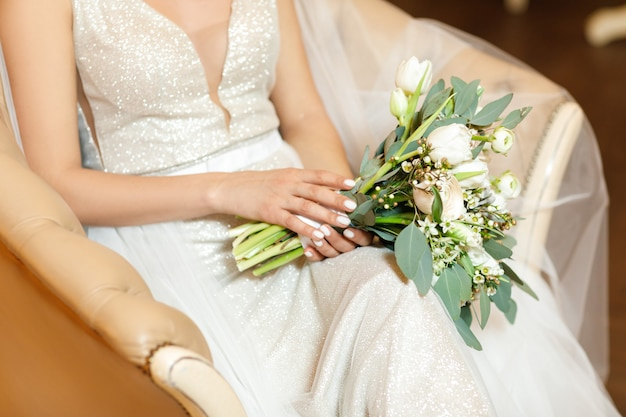 Bride's hands hold beautiful bridal bouquet