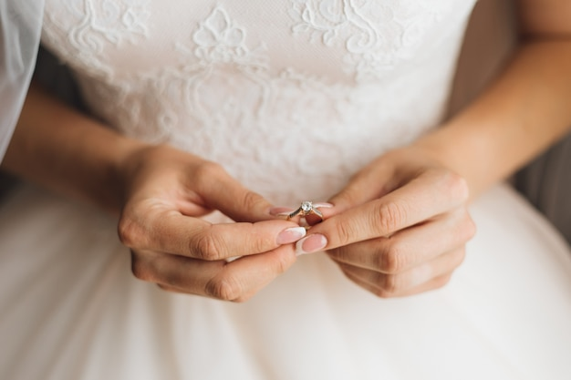 Bride's hands hold the beautiful engagement ring with gemstone, close up, without face