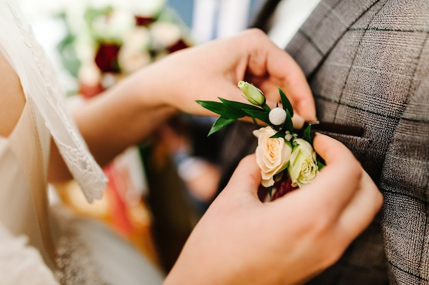Bride's hands puts the groom on jacket a wedding boutonniere. wedding concept.