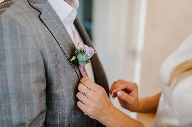 Руки невесты надевают жениха на пиджак свадебной бутоньерки. свадебная концепция.
