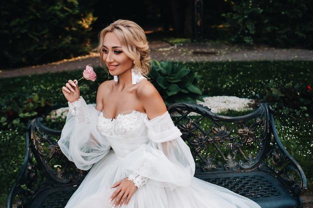 庭での花嫁の朝。庭の木にぶら下がって、彼女のウェディングドレスを見ている若い花嫁の肖像画。