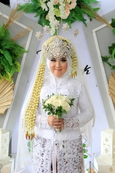 The bride's portrait wears a traditional javanese and muslim dress