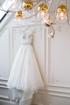 Bride's shoes hang on the chandelier in the interior of a luxury hotel