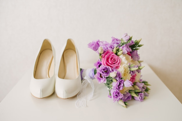 The bride's shoes and pink lilac wedding bouquet lies next to the white background, the bride's accessories