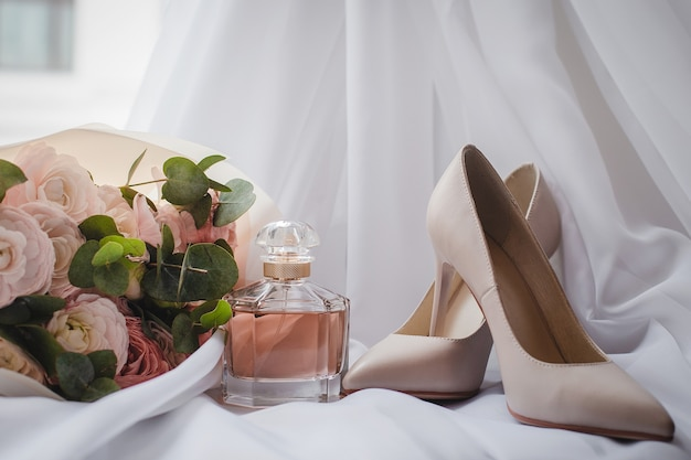 A bride's shoes with a wedding bouquet and perfume on the veil. wedding concept