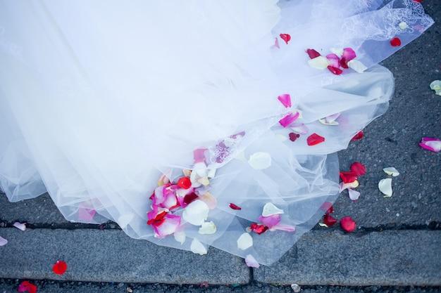 ピンクの花びらを持つ花嫁のウェディングドレス