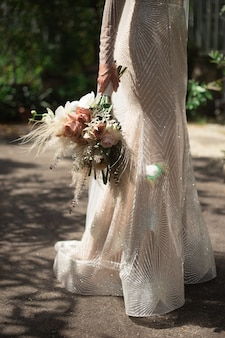 A bride in a shiny wedding dress stands and holds a boho style wedding bouquet in her hand.