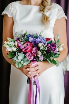 Невеста демонстрирует свой прекрасный букет из розовых, фиолетовых, пурпурных цветов. идеальный образ с копией пространства для шикарных свадебных журналов и веб-сайтов, богемы, модного стиля, флориста.