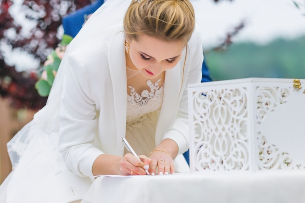 The bride signs on the document. wedding ceremony. close up.