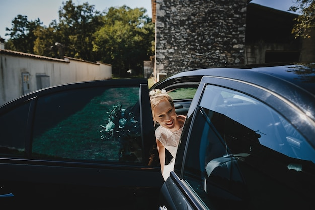 Bride sits down in the car