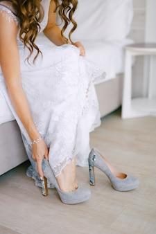 Невеста сидит на кровати и надевает туфли на высоких каблуках в гостиничном номере во время подготовки к свадьбе