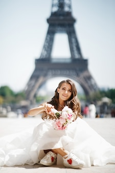 Bride sits in snickers before the eiffel tower in paris