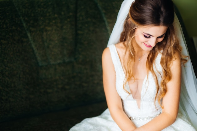 Bride sits on sofa in wedding dress with wedding veil and smiles