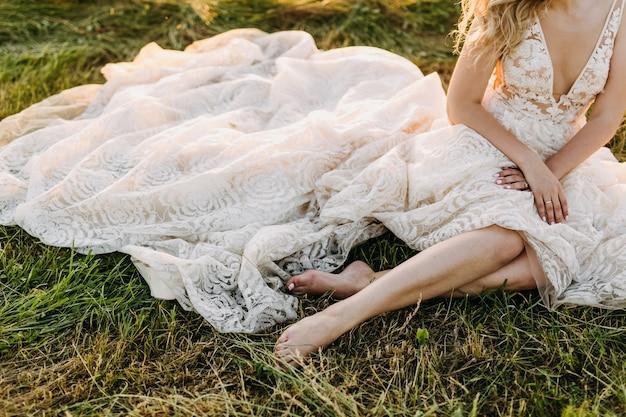 長いウェディングドレスを着て、草の上に座っている花嫁。