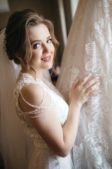 The bride smiles while holding a wedding dress
