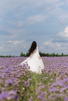 Bride spinning a field of flowers in the summer on the wedding day