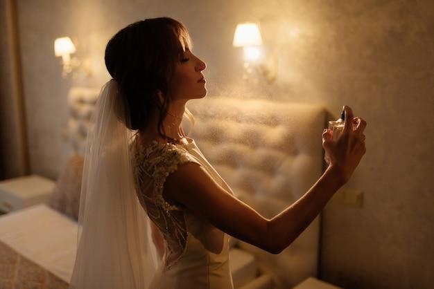 白いドレススプレー柔らかい香水を身に着けている花嫁スプレー香水スタイリッシュな女性。手で香水のスタイリッシュなガラス瓶。化粧と香水のボトルを持つ少女。結婚式の準備。