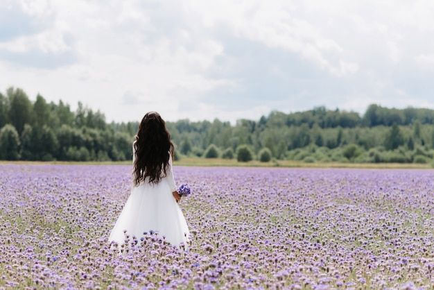 Bride stand in a field of flowers in the summer on the wedding day
