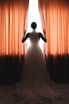 外を見て窓に立っている花嫁