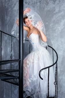 Невеста, стоящая на винтовой лестнице в квартире-лофте, женщина, одетая в свадебное платье с кружевной копией ...
