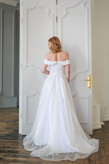 The bride stands back showing off a beautiful wedding dress from the back