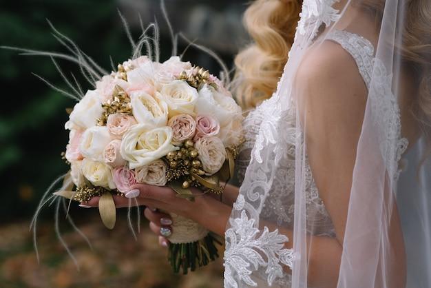신부 부케와 하얀 웨딩 드레스에 서