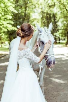 Bride stands near white horse