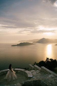 The bride stands on the observation deck overlooking the island at the sunset back view