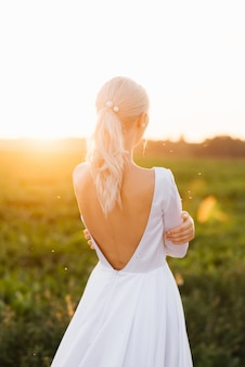 Bride stands with his back to the sunset