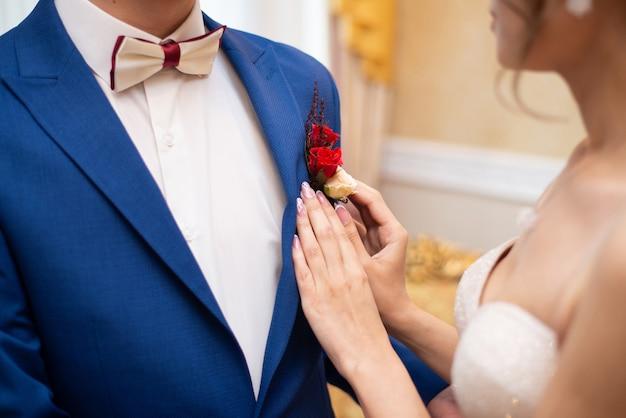 花嫁は彼女の妻にバラのブートニアをまっすぐにします