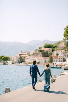 The bride in a stylish blue dress and groom walk along the pier holding hands near the old town of perast, back view . high quality photo