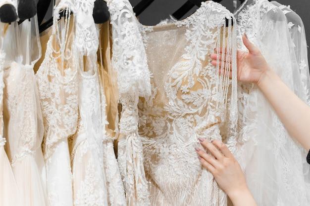 Bride touches luxurious white cream wedding dress on hangers.