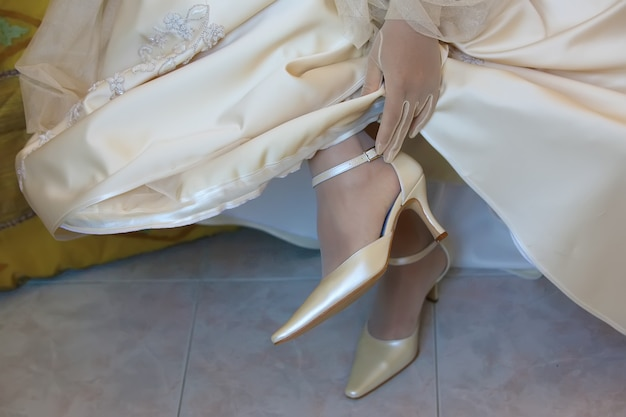 The bride touches the strap of shoes