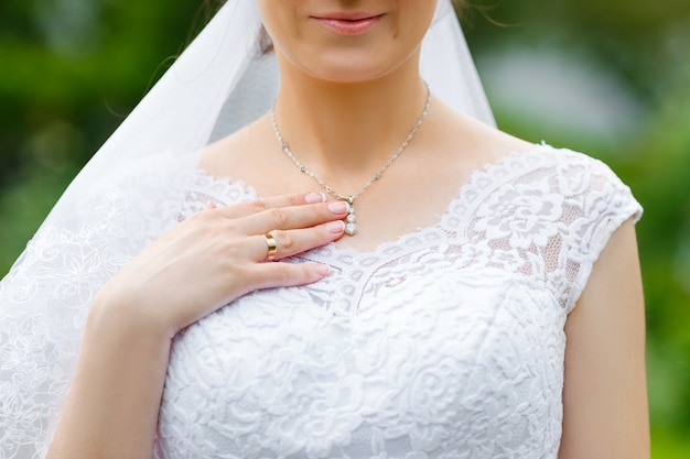 Bride touching shiny diamond pendant