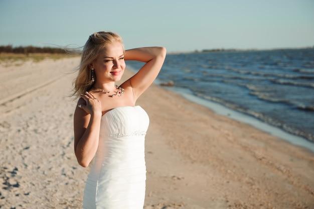 Bride walking along sea coast wearing beautiful wedding dress.
