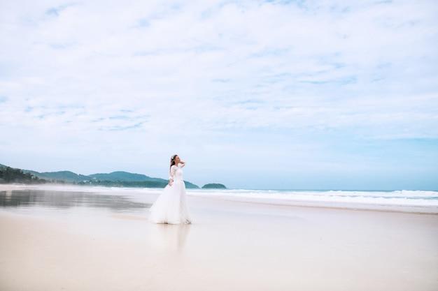웨딩 드레스를 입고 해변에 산책하는 신부