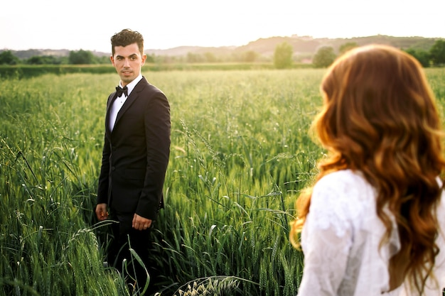 Bride walks to italian groom standing on green field