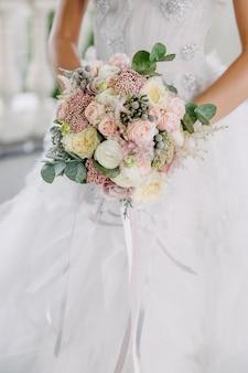 さまざまな花で作られたブライダルブーケを持って、レースの白いドレスを着ている花嫁。