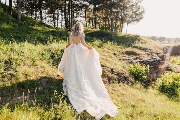 背中が開いた長いウェディングドレスを着ている花嫁