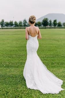 開いた背中の長い白いエレガントなウェディングドレスを着ている花嫁