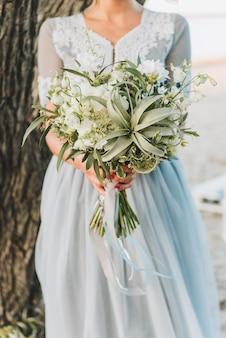 Bride wearing light blue wedding dress holding bouquet